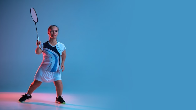 Mouvement. belle femme naine pratiquant le badminton isolé sur bleu à la lumière du néon