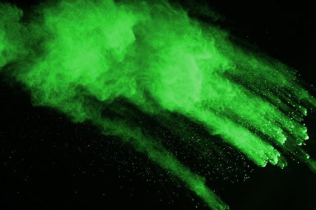 Le mouvement d'explosion de poussière abstraite gelé vert sur fond noir.