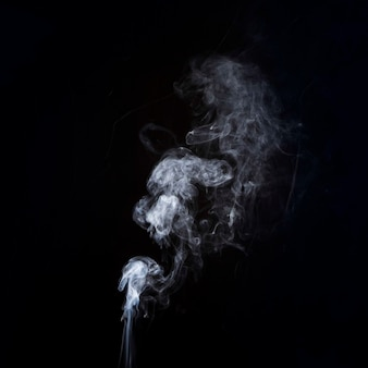 Mouvement de fumée blanche sur fond noir avec espace de copie pour l'écriture du texte