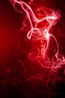 Mouvement De Fumée Rouge Sur Fond Noir. Photo Premium