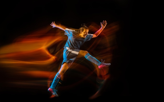 Mouvement. joueur de football ou de soccer sur fond de studio noir en lumière mixte. jeune modèle sportif masculin s'entraînant en action. frapper le ballon, attaquer, attraper. concept de sport, de compétition, de victoire.