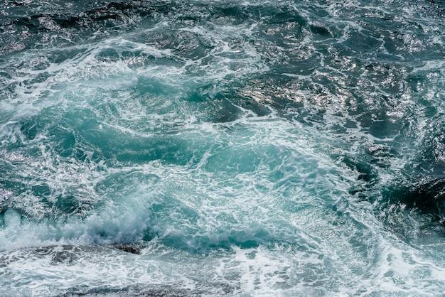 Mouvement de la surface de l'eau de mer avec pierre, éclaboussures d'eau bleue