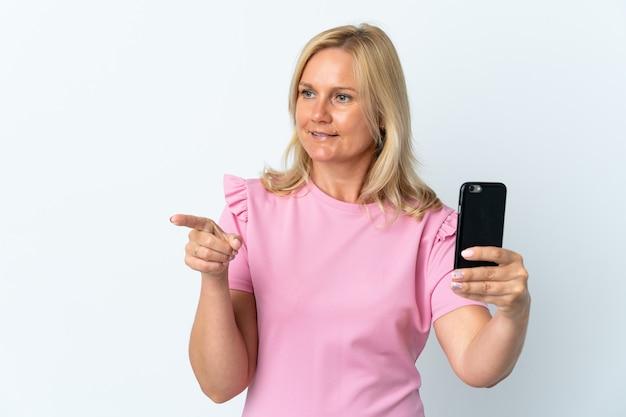 Moyen âge à l'aide de téléphone mobile isolé sur un mur blanc pointant vers le côté pour présenter un produit