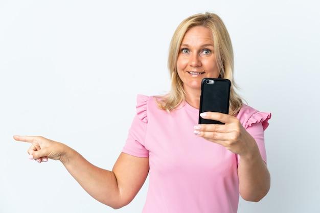 Moyen âge à l'aide de téléphone mobile isolé sur un mur blanc surpris et pointant le doigt sur le côté