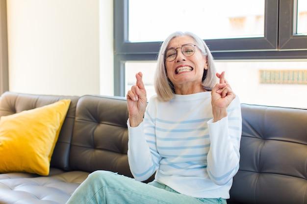 Moyen-âge jolie femme souriante et croisée anxieusement les deux doigts, se sentant inquiète et souhaitant ou espérant avoir de la chance