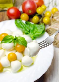 Mozzarella fraîche aux tomates jaunes et basilic.