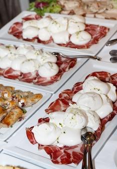 Mozzarella traditionnelle des pouilles et collations antipasti lors d'un mariage ou d'une célébration italiens, vue ci-dessus. réception festive avec divers plats nationaux. restauration continentale de vacances, cuisine méditerranéenne