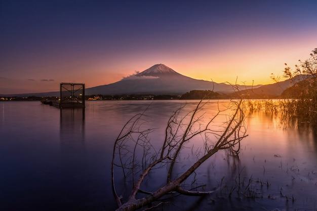 Mt. fuji sur le lac kawaguchiko avec arbre mort au coucher du soleil à fujikawaguchiko, au japon.