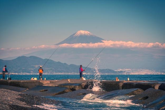 Mt. fuji avec des pêcheurs au coucher du soleil dans la préfecture de shizuoka, au japon.
