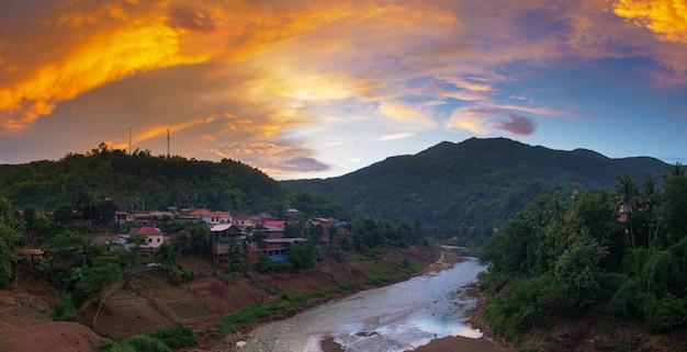 Muang khua village dans les montagnes du nord du laos, coucher de soleil ciel dramatique. petit village laotien dans la vallée de la rivière. destination de voyage pour la randonnée tribale dans les villages akha