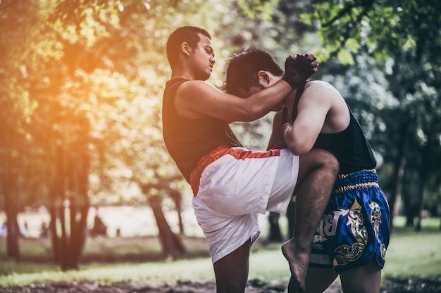 Muay thai arts martiaux ou la boxe thaïlandaise, deux jeunes combattants kickbox formation dans le parc