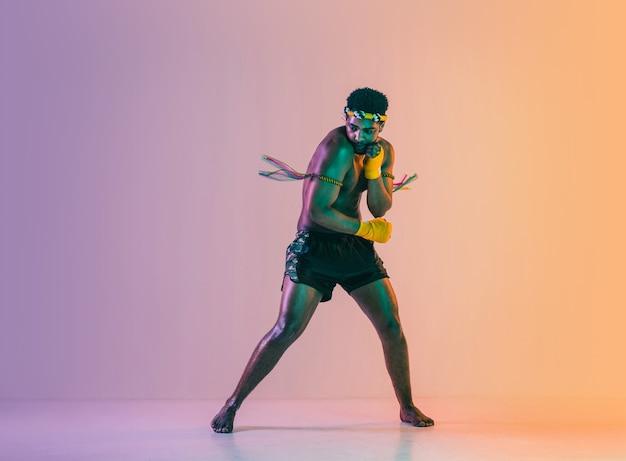 Muay thaï. jeune homme exerçant la boxe thaï sur fond dégradé en néon. combattant pratiquant, entraînement aux arts martiaux en action, mouvement. mode de vie sain, sport, concept de culture asiatique.