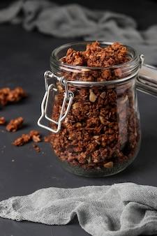 Muesli croustillant granola avec du miel naturel, du chocolat et des noix dans un bocal en verre sur un fond sombre