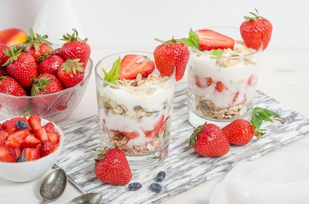 Muesli avec du yaourt et des fraises fraîches sur un fond en bois blanc.