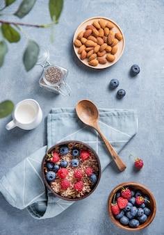 Muesli énergétique aux framboises, myrtilles, graines de chia, noix d'amande et lait dans un bol de noix de coco sur fond bleu. vue de dessus
