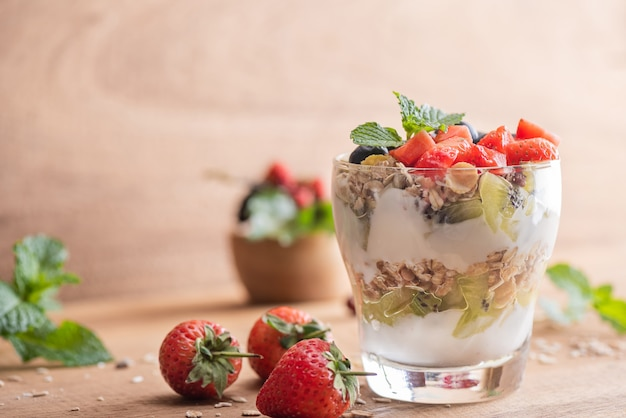 Muesli fait maison, bol de granola d'avoine avec yaourt, myrtilles fraîches, mûres, fraises, kiwi, menthe et noix pour un petit-déjeuner sain, espace de copie. concept de petit-déjeuner sain. manger propre.
