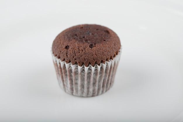 Muffin au chocolat avec dessus croustillant placé sur une assiette blanche.