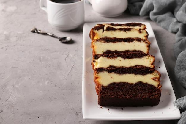 Muffin au chocolat fait maison en tranches avec du fromage cottage situé sur une plaque blanche sur fond gris