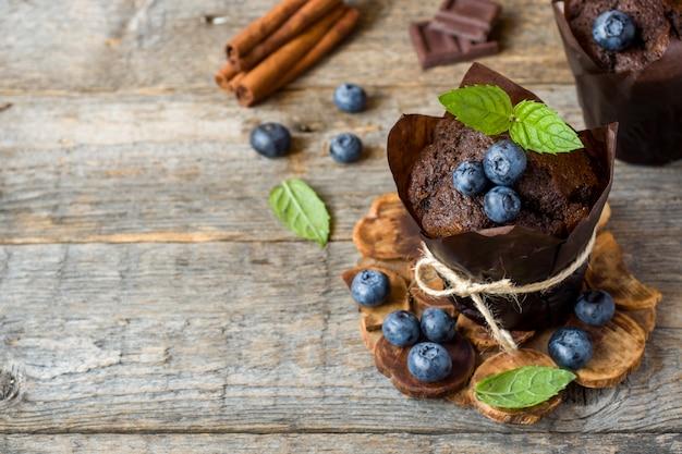 Muffin au chocolat à la menthe et bleuets sur socle en bois