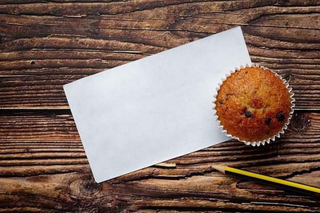 Muffin au chocolat, papier blanc vide et un crayon posé sur un plancher en bois