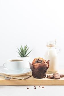 Muffin au chocolat et tasse de chocolat avec du lait et des pépites de chocolat sur fond blanc.