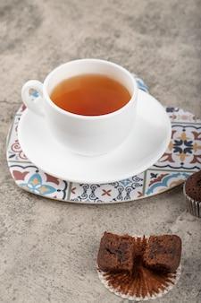Muffin au chocolat avec une tasse de thé blanc posé sur une table en pierre.