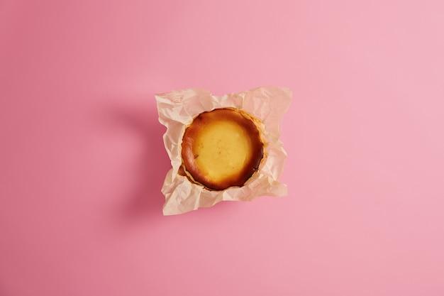 Muffin au fromage fait maison emballé dans un emballage en papier isolé sur fond rose. confiserie riche en calories de la boulangerie. collation sucrée ou petit-déjeuner. produit de boulangerie préparé par un chef gastronomique.