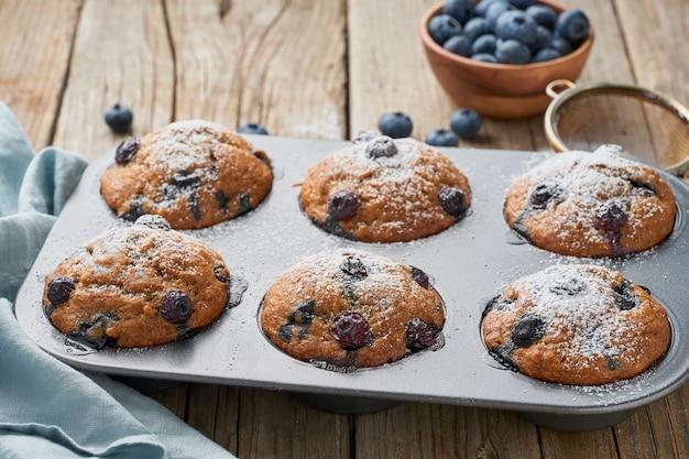 Muffin aux bleuets dans un plateau, vue de côté. petits gâteaux avec des baies dans un plat allant au four sur une vieille serviette en lin