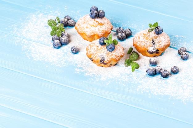Muffin aux myrtilles. petit gâteau cuit au four avec des myrtilles, des baies fraîches, à la menthe sur fond en bois.