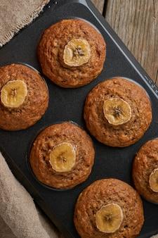 Muffin à la banane dans un plateau, vue de dessus, vertical. petits gâteaux sur une vieille serviette en lin, table en bois rustique
