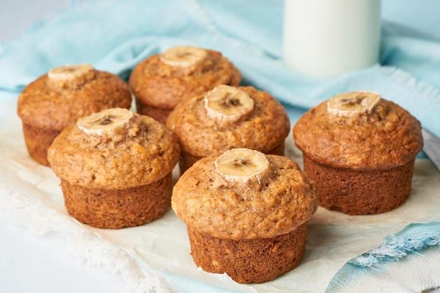 Muffin à la banane, vue de côté, gros plan. petits gâteaux sur une serviette bleue avec du lait en croûte, béton blanc