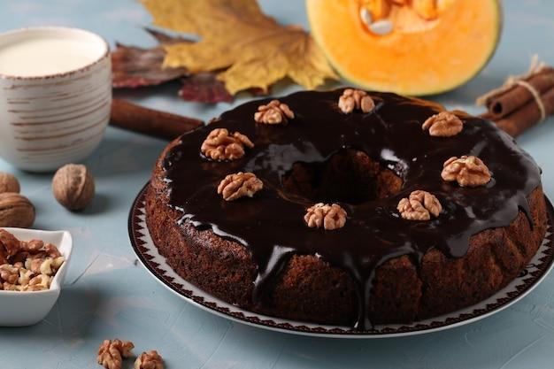 Muffin à la citrouille maison décoré de glaçage au chocolat et de noix sur fond bleu clair