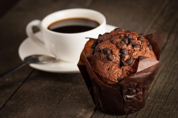 Muffin cuit au chocolat noir à la menthe sur une table en bois avec cannelle, anis, chocolat.