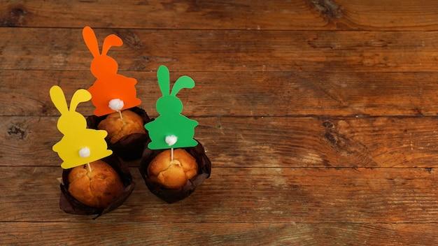 Muffin décoré d'un lapin en papier sur un cure-dent. décor de pâques pour les cupcakes. confiseries et pâtisseries festives. fond en bois