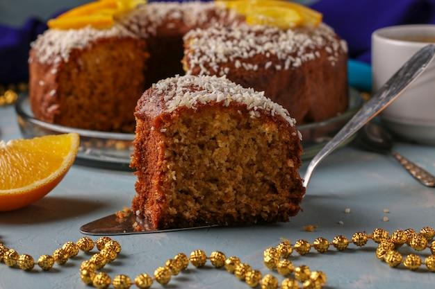 Muffin fait maison avec des oranges saupoudrées de flocons de noix de coco sur une surface bleu clair