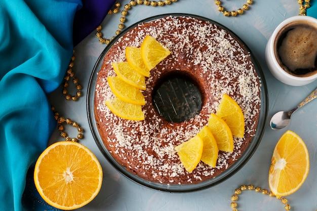 Muffin maison aux oranges avec un trou au centre, saupoudré de flocons de noix de coco