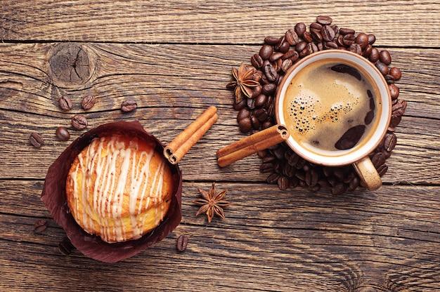 Muffin savoureux et tasse à café sur table en bois vintage