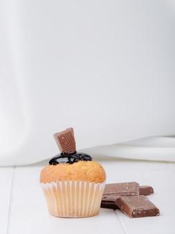 Muffin vue de face avec glaçage au chocolat et chocolat sur une surface blanche