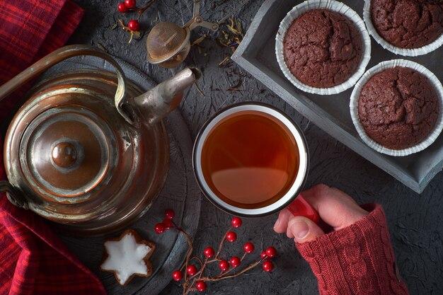 Muffins au chocolat, biscuits, théière et décorations d'hiver