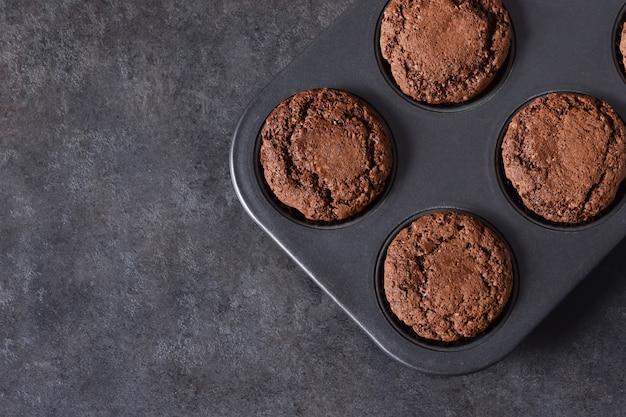 Muffins au chocolat, brownies aux noix et chocolat sur fond noir