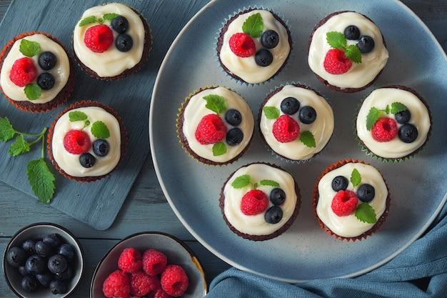 Muffins au chocolat ou cupcakes à la crème fouettée et aux baies, à plat