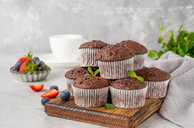 Muffins au chocolat ou cupcakes avec des gouttes de chocolat sur une planche en bois avec des baies fraîches et de la menthe