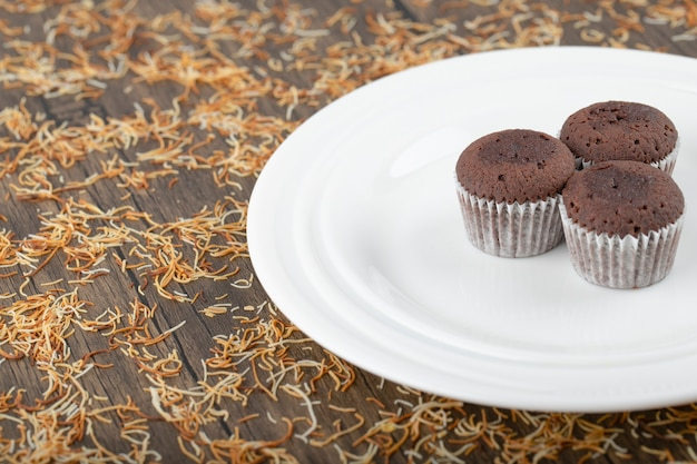 Muffins au chocolat dans du papier blanc placés dans une assiette blanche.