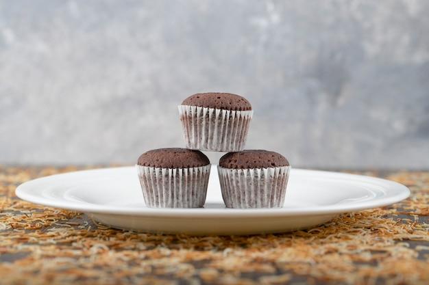 Muffins au chocolat avec dessus croustillant placés sur une assiette blanche.
