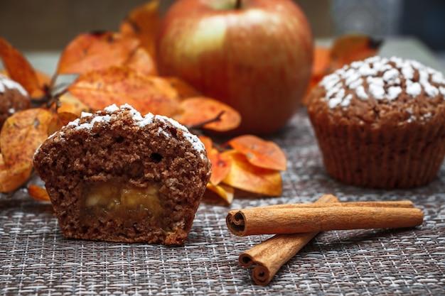Muffins au chocolat avec garniture aux pommes sur fond de feuilles d'automne et cannelle
