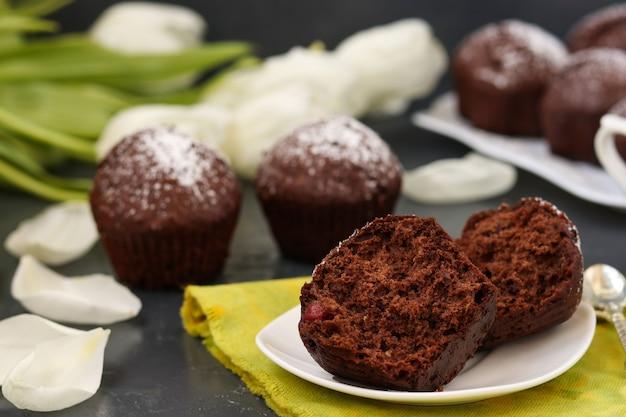 Muffins au chocolat maison à la cerise, recouverts de sucre en poudre situé sur une surface sombre