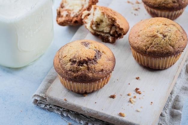 Muffins au chocolat et à la vanille faits maison à partir de deux types de pâte avec un bocal de lait