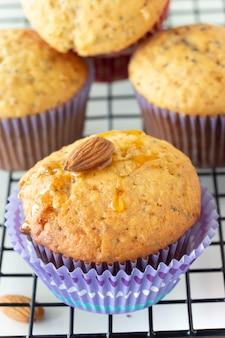 Muffins au citron faits maison avec des bonbons au chocolat colorés dans une caisse en papier et une tasse de thé