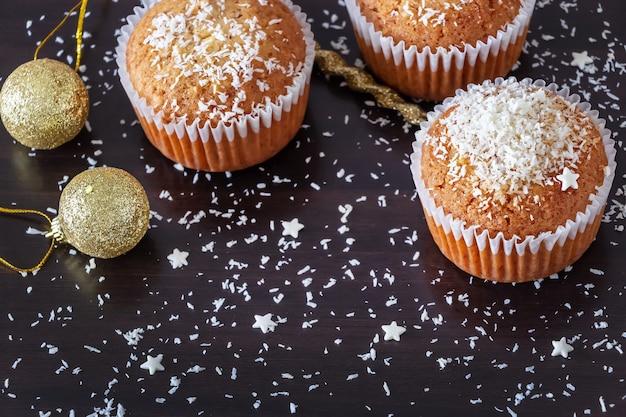 Des muffins au citron faits maison décorent la poudre de noix de coco sur du bois foncé