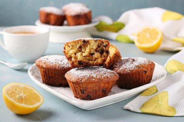 Muffins au citron faits maison avec du chocolat sur une plaque blanche sur un bleu clair.